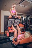 attractive women in gym on workout machine