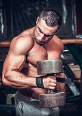 Muscular bodybuilder doing exercises with dumbbells