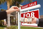 Handing Over Cash For House Keys And Short Sale Sign