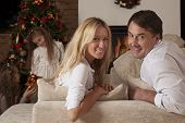 Happy Couple Sitting On The Couch With Christmas Tree