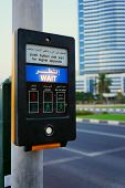 Button On The Pedestrian Crosswalk In Sharjah With Blurred Buildings And Road In The Background