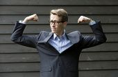 Young Businessman Flexing His Muscles