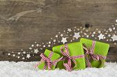 Green christmas presents on wooden background for a gift certificate.