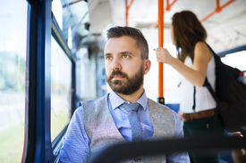 stock photo of tram  - Handsome hipster modern man traveling by tram in town - JPG