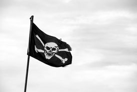 stock photo of skull crossbones flag  - Ragged pirate flag with skull and crossbones flying from flagpole  - JPG
