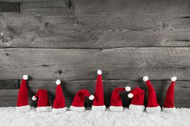 stock photo of timber  - Wooden christmas background with red santa hats for a festive frame or card - JPG