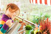 Adorable little girl watering plants on the balcony on a nice sunny day