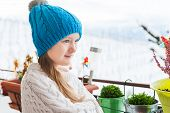 Adorable little girl watching the snow from the balcony, wearing winter hat and warm white pullover