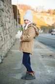 Outdoor portrait of a cute little girl in a city, wearing warm winter beige coat and blue boots, hol