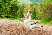 Cute little girl playing on a chain swing, having fun in a park on a nice autumn day