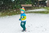 Winter portrait of a cute little boy under the snowfall, wearing christmas pullover and colorful hat
