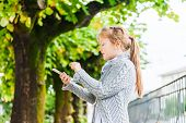 Outdoor portrait of a cute little girl using the phone