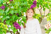 Outdoor portrait of a cute little girl against beautiful lilac on a nice spring day
