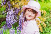 Spring portrait of adorable little girl, wearing rain hat and coat