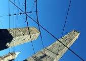 stock photo of tram  - ancient tower called DEGLI ASINELLI in Bologna Center in Italy with tram wires - JPG