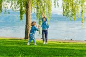 Two kids having fun outdoors on a nice sunny day, playing by the lake