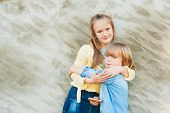 Outdoor portrait of adorable kids hugging each other