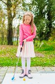 Cute little girl playing mini golf in a park