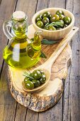 stock photo of kalamata olives  - Wooden spoon and bowl with green olives and a jar with olive oil on a cutting board on the table of the kitchen - JPG