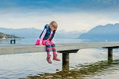 Adorable little girl sitting on a pier by the lake and swinging legs in the air