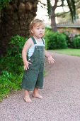 Adorable toddler boy on vacations, wearing green overalls