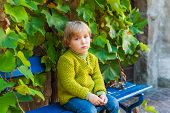 Sad toddler boy sitting on a bench outdoors