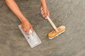 picture of concrete pouring  - Close up of hand using steel trowel to finish wet concrete floor of polished concrete surface - JPG