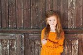 Outdoor portrait of a cute little girl standing next wooden door, wearing bright orange pullover