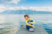 Cute little girl resting on a pier on a sunny summer day