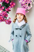 Outdoor portrait of a cute little girl, wearing grey coat and pink hat