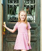 Outdoor portrait of adorable little girl in a pink dress