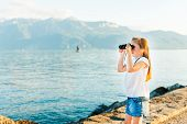 Cute little girl standing next to beautiful lake on sunset and looking in binoculars