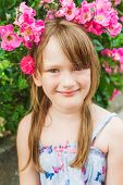 Summer portrait of a cute little girl with pink rose in hair