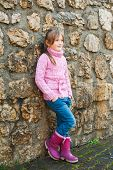 Outdoor portrait of adorable little girl wearing pink pullover