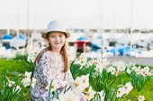 Spring portrait of adorable little girl by the lake, resting in a park between white narcissus, wear
