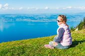 Cute little girl resting on the top of the mountain and looking on a beautiful lake