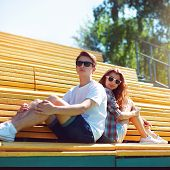 Fashion Hipster Couple In Sunglasses Sitting On The Bench City Park In Sunny Summer Day