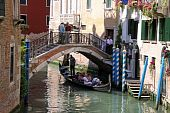 Gondolier and tourists in a gondola in Venice