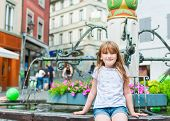 Outdoor portrait of adorable little girl playing in a city on a nice summer day