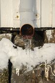Icicles Hanging From Frozen Iron Drainpipe