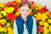 Outdoor portrait of adorable little girl against colorful flowers