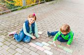 Children playing outdoors on a nice sunny day, drawing with chalk