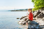 Adorable little boy boy playing by the lake on a very hot summer day, holding bottle of water