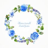 Round frame of watercolor blue flowers and berries.