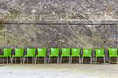 image of salt mine  - Green plastic chairs in raw near a wall in a salt mine - JPG