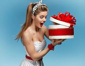 Portrait of happy woman opening gift box against blue background. Holidays, holiday, celebration, bi