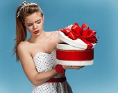 Thoughtful girl holding holiday or birthday presents, gift box on blue background. Holidays, celebra
