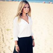 Young Beautiful Woman Blonde Poses On A Beach