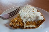 foto of pumpkin pie  - Whipped pumpkin pie slice with cream on top on a plate - JPG