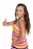 stock photo of preteen  - A smiling preteen girl holds her thumb up against the white background - JPG